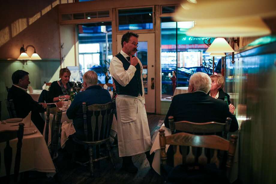 Server Matthew Weimer (center) chats with Lucille and Frank Ferguson at Cafe Jacqueline in San Francisco. Photo: Gabrielle Lurie, The Chronicle