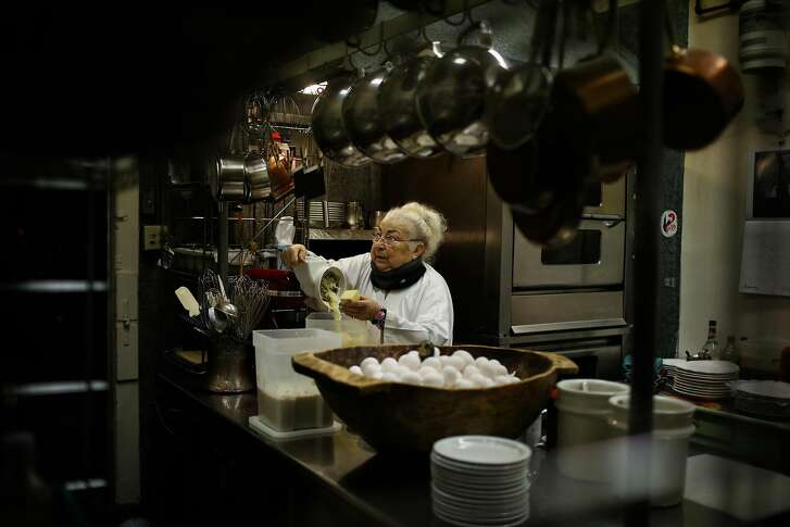 Chef Jacqueline Margulis grates cheese while preparing food at Cafe Jacqueline in San Francisco, California, on Wednesday, Jan. 31, 2018.