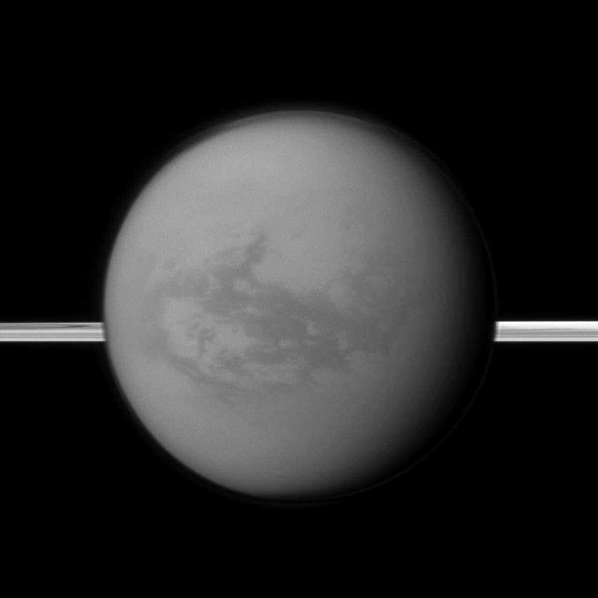 This image shows Titan with Saturn's rings in the background. Titan holds liquid, has clouds and experiences rain. But unlike Earth, Titan's bodies of liquid contain methane, not water, according to NASA.