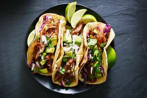 mexican street tacos flat lay composition with pork carnitas, avocado, onion, cilantro, and red cabbage