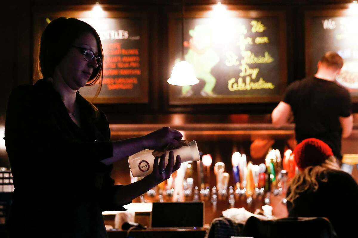 Bartender Katie Cox cleans glasses as employees prepare the new Ginger Man location in Midtown for its soft open Monday, Feb. 12, 2018 in Houston. (Michael Ciaglo / Houston Chronicle)