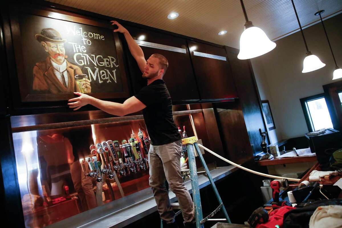 Bartender Josh Winkelmann hangs a sign above the bar as employees prepare the new Ginger Man location in Midtown for its soft open Monday, Feb. 12, 2018 in Houston. (Michael Ciaglo / Houston Chronicle)