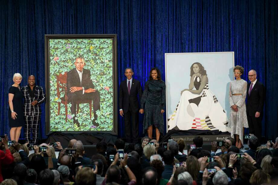 Former President Barack Obama and former first lady Michelle Obama stand with their official portraits Monday at the National Portrait Gallery, along with the artists who painted them. Photo: GABRIELLA DEMCZUK, STR / NYTNS