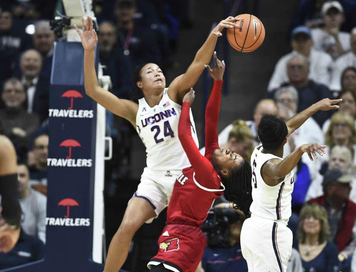 UConn's Napheesa Collier (24) blocks a shot by Louisville's Dana Evans Monday in Storrs.