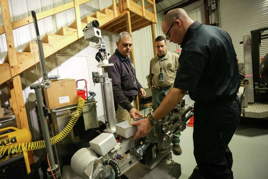 Montgomery County Assistant Fire Marshal Kevin Bates, center, and investigator Joe Manz, left, and investigator Jimmy Ballinger, right, perform maintenance on a Remotec Andros Mark 5A-1 on Monday, Feb. 12, 2018, in their facility at Conroe-North Houston Regional Airport. Photo: Michael Minasi, Staff Photographer / © 2017 Houston Chronicle