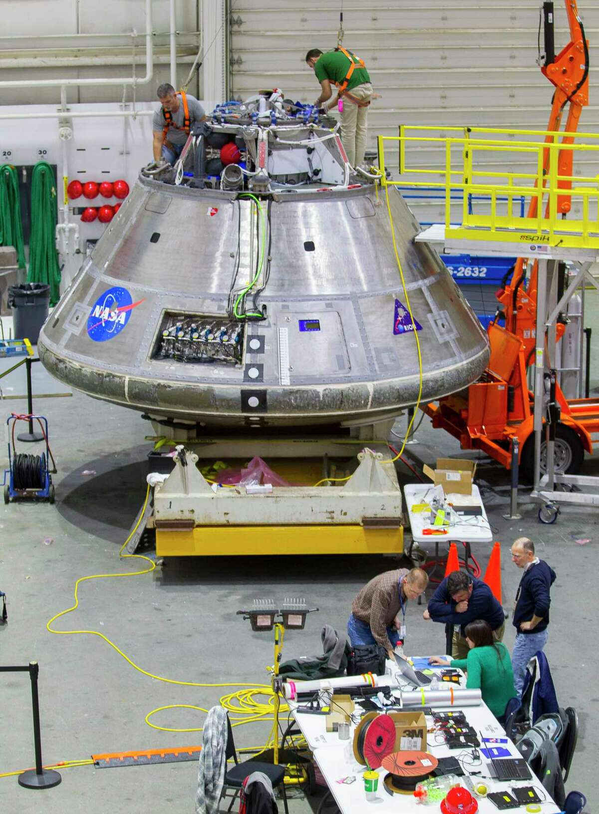 Workers make adjustments to an Orion capsule being used for training at the Neutral Buoyancy Laboratory, Monday, Feb. 12, 2018, in Houston.