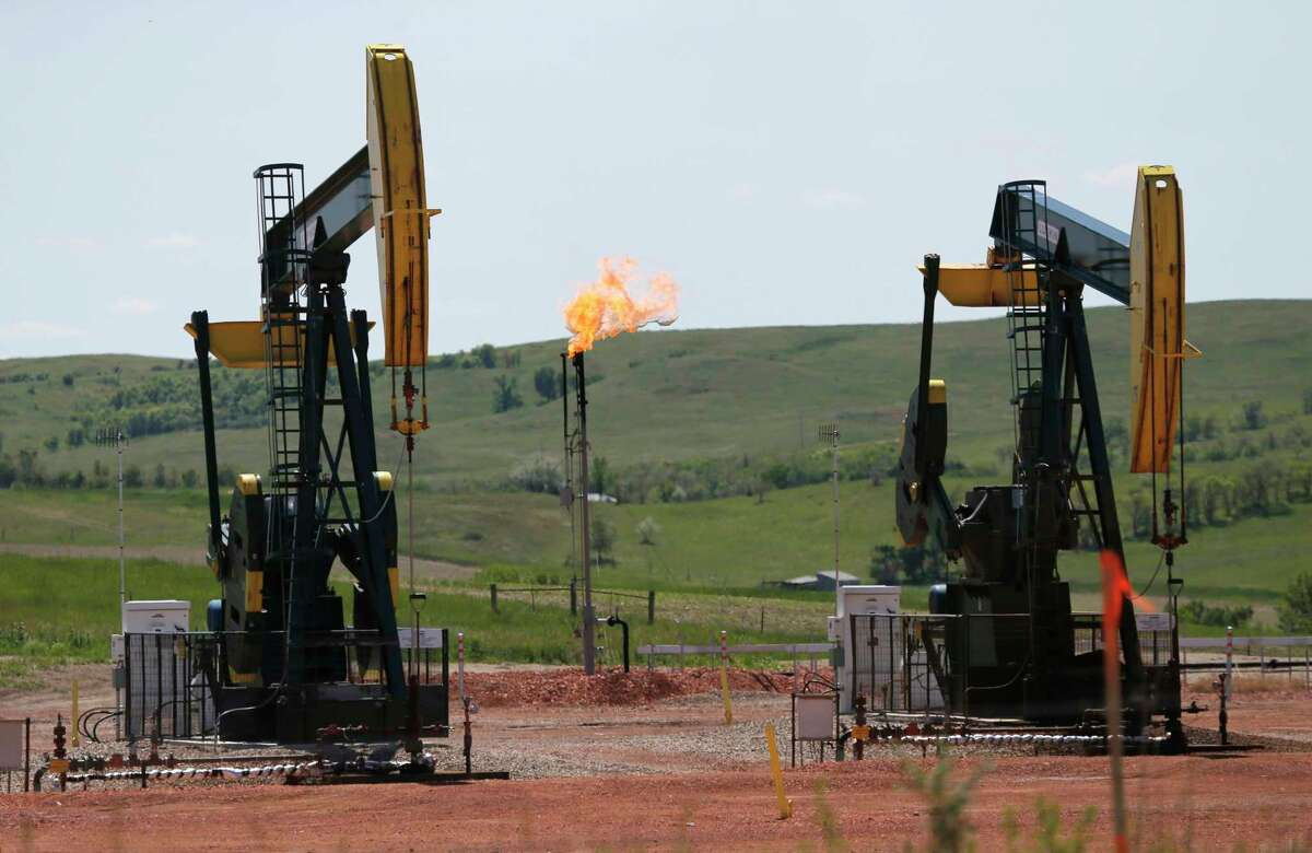 FILE -In this June 12, 2014 file photo, oil pumps and natural gas burn off in Watford City, N.D. (Photo/Charles Rex Arbogast, File)