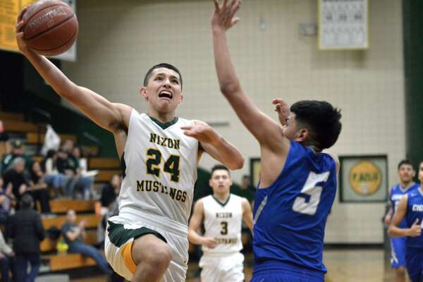 Neal Garcia drives to the basket for the Nixon Mustangs as Miguel Gallegos defends for the Cigarroa Toros, Monday, February 12, 2018, at Nixon.