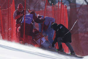 Officials assist Russia's Pavel Trikhichev after he crashed during the downhill portion of the men's combined at the 2018 Winter Olympics in Jeongseon, South Korea, Tuesday, Feb. 13, 2018.