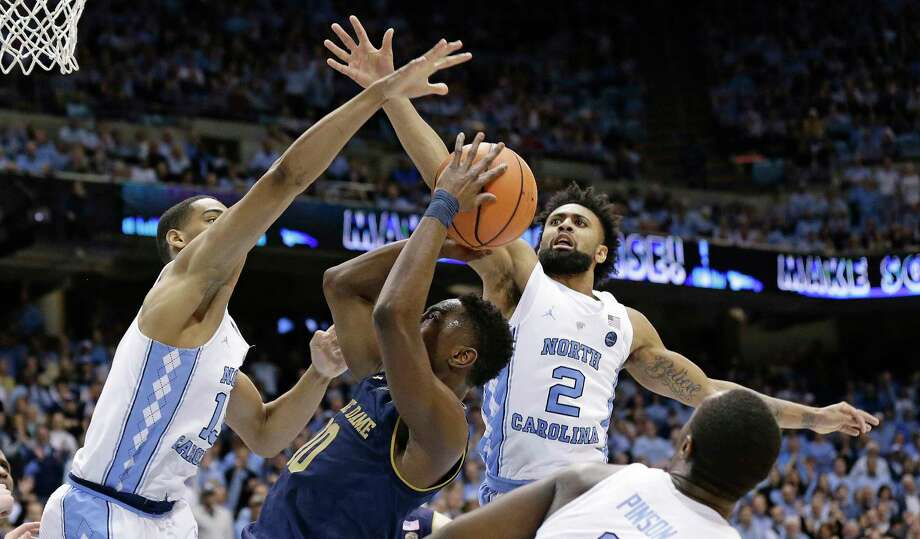 North Carolina's Garrison Brooks, left, and Joel Berry II (2) guard Notre Dame's T.J. Gibbs (10) during the second half of an NCAA college basketball game in Chapel Hill, N.C., Monday, Feb. 12, 2018. North Carolina won 83-66. (AP Photo/Gerry Broome) Photo: Gerry Broome, STF / Copyright 2018 The Associated Press. All rights reserved.