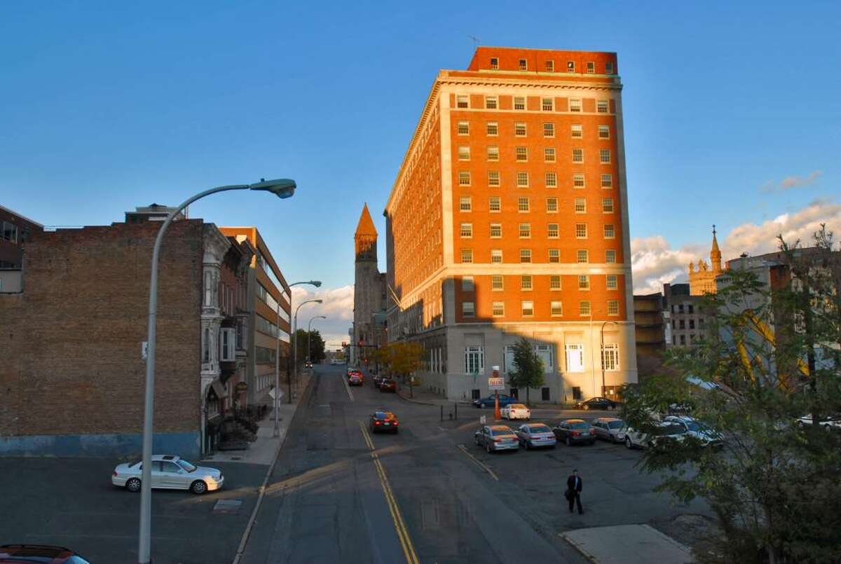 The last rays of sun light up the DeWitt Clinton building on Eagle Street in Albany Tuesday. The mostly vacant site would shine again as an Embassy Suites Hotel with the help of a $4 million state grant. The owner vows to pay back taxes and other bills. (Philip Kamrass / Times Union)