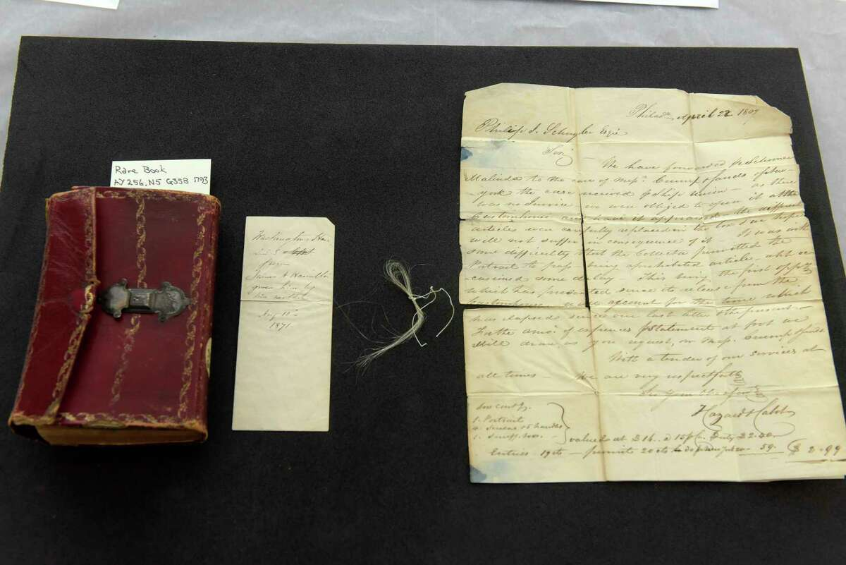 From left to right, a view of a book, Gaine's Universal Register, that is believed to have belonged to Philip J. Schuyler, an envelope that was inside the book and some strands of hair of George Washington's hair and a letter written to Philip J. Schuyler, seen here at Union College on Thursday, Feb. 8, 2018, in Schenectady, N.Y. Philip J. Schuyler was the son of General Philip Schuyler. (Paul Buckowski/Times Union)