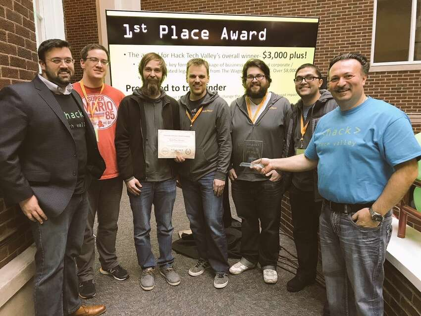 Antonio Civitella, CEO of Transfinder, gives the first place award to software coders from Auto/Mate at Hack Tech Valley on Sunday at Schenectady County Community College.