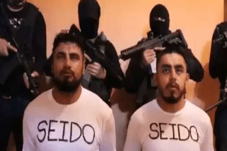 A  video screenshot published by Blog Del Narco  apparently shows two kneeling, bound Mexican intelligence agents surrounded by five masked gunmen. A federal official said Monday the two men are apparently the two agents of the federal Attorney General's Office who went missing Feb. 5 in the Pacific coast state of Nayarit.