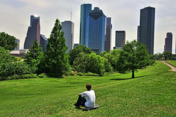 A teen contemplates the Houston skyline while resting on his skateboard in the park during his summer vacation