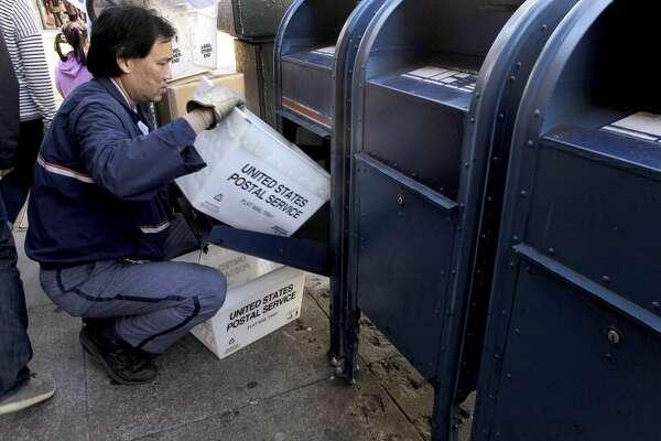 A mail carrier empties a mailbox.