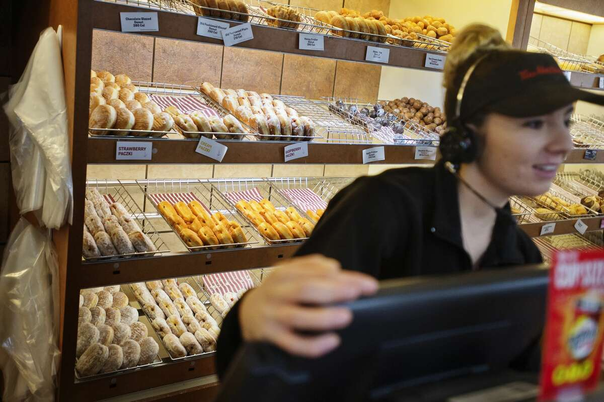 Paczki are arranged in a display case while Tim Horton's employee Celia Eastman assists a customer on Fat Tuesday, Feb. 13, 2018, at the S. Saginaw Road location in Midland. (Katy Kildee/kkildee@mdn.net)