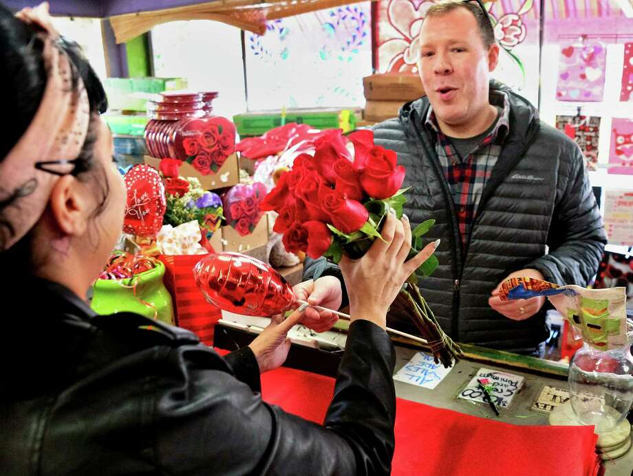 Dale Webster of Chatham buys Valentine's Day roses from store manager Tiffany Barkevich, left, at Lark St. Flower Market on Tuesday, Feb. 13, 2018, in Albany, NY.  (John Carl D'Annibale/Times Union) Photo: John Carl D'Annibale, Albany Times Union / 20042920A