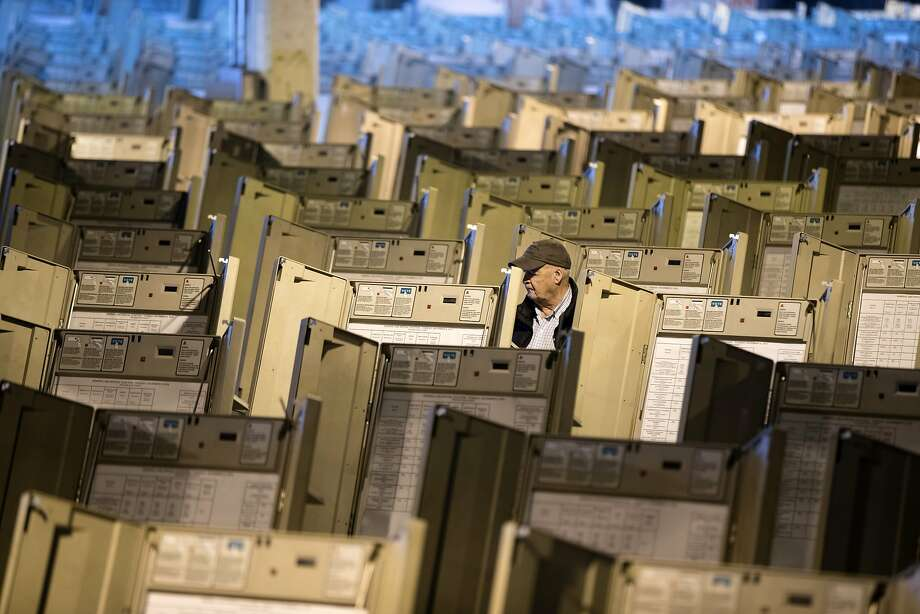 A technician prepares voting machines before the 2016 election in Philadelphia. Experts say little has been done to shore up obsolete technology. Photo: Matt Rourke, Associated Press