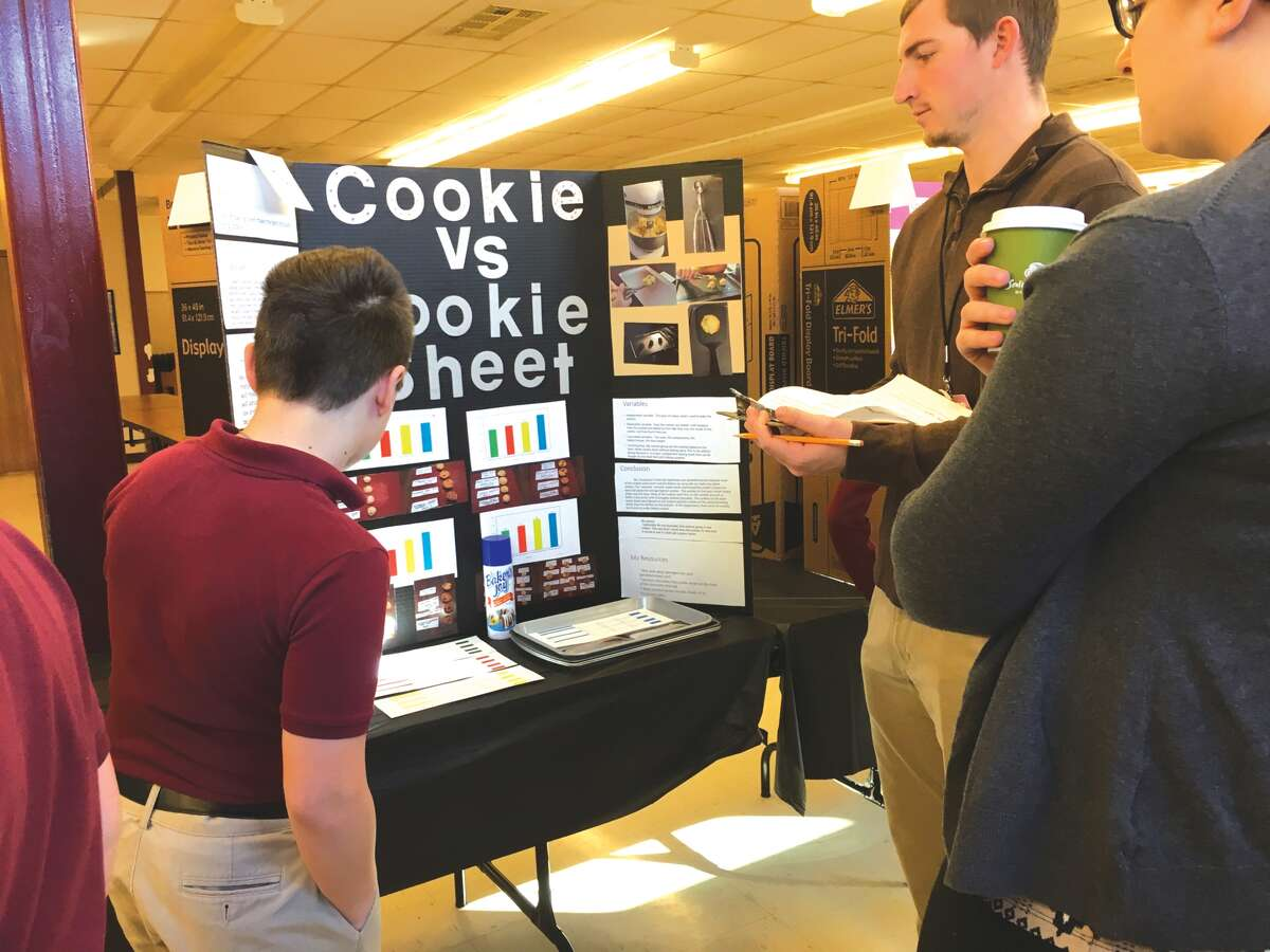 St. Mary's Catholic School seventh grader Reece Kleinschmidt explains his science fair project to judges on Monday. Open to students in grades one through eight, the event was judged by SIUE chemistry and biology students.