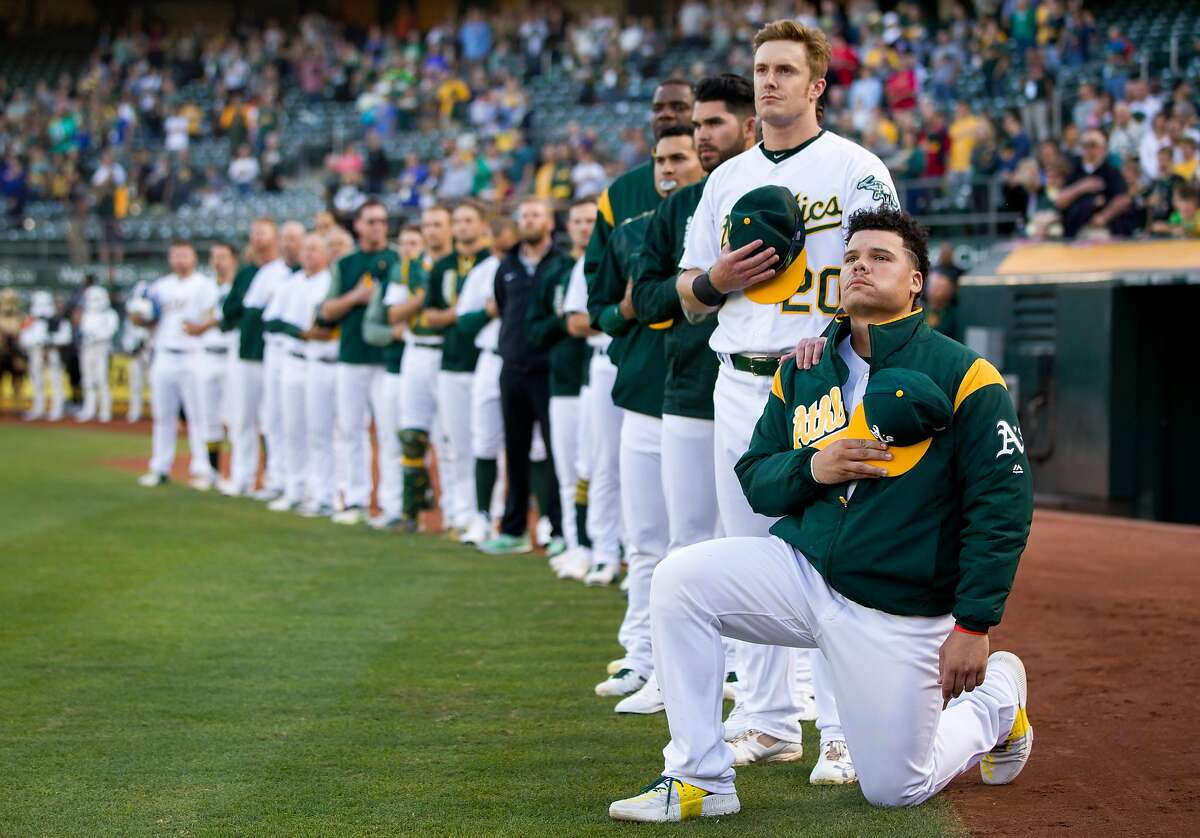 From right: Oakland Athletics catcher Bruce Maxwell (13) takes a knee as Oakland Athletics left fielder Mark Canha (20) puts his hand on his shoulder during the playing of the national anthem before an MLB baseball game between the Oakland Athletics and Texas Rangers at the Oakland Coliseum on Saturday, Sept. 23, 2017, in Oakland, Calif.