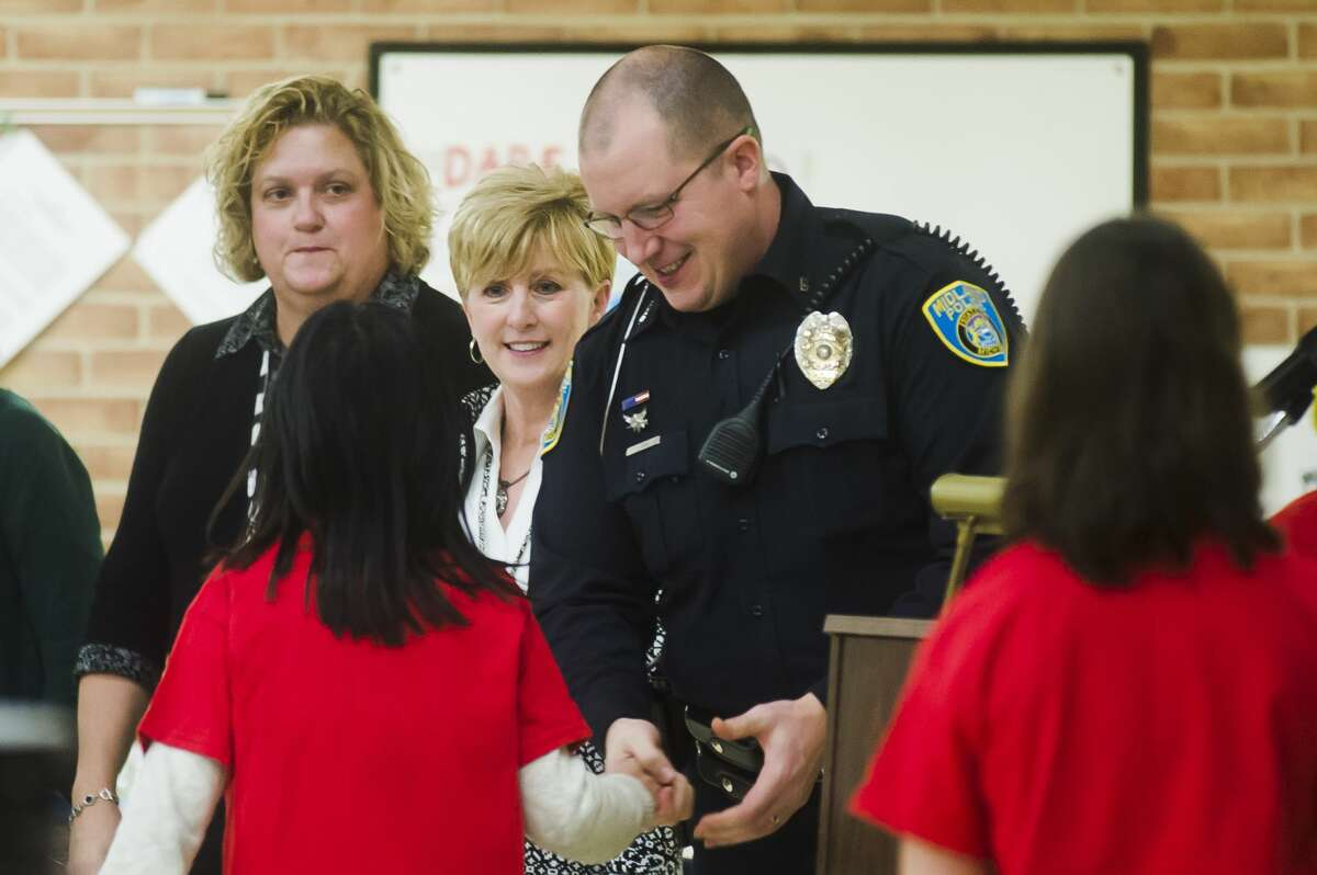 Officer Jeremy Davis of the Midland Police Department shakes hands with each student during their D.A.R.E. graduation at Adams Elementary, where Davis has taught D.A.R.E. for the past nine years, on Tuesday, Feb. 13, 2018. Davis is now a part of the department?•s detective bureau. (Katy Kildee/kkildee@mdn.net)