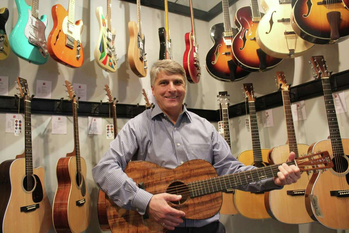 Phil Williams and his many guitars at New Canaan Music on Monday.