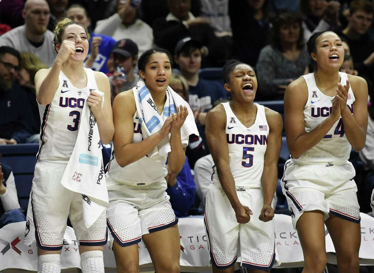 Connecticut's Katie Lou Samuelson (33), Gabby Williams (15), Crystal Dangerfield (5), and Napheesa Collier (24) cheer from the bench in the closing seconds of an NCAA college basketball game against Tulane, Saturday, Jan. 27, 2018, in Storrs, Conn. UConn won, 98-45. (AP Photo/Stephen Dunn)