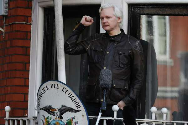 Julian Assange, founder of WikiLeaks, holds up a fist before speaking to media and supporters from a balcony at the Ecuadorian embassy in London in May, 2017. Assange hailed a Swedish decision to drop a rape probe against him. Tuesday, however, a British judge denied Assange's lawyer's request to lift a British warrant against him.