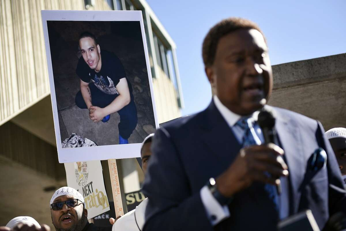 A picture of the Shaleem Tindleis seen behind Attorney John Burris, who is representing Shaleem's family, as speaks to the crowd during a rally at the West Oakland BART station in Oakland, CA, on Tuesday February 13, 2018. Shaleem Tindle, a 28-year-old African-American man and father of two minor children, was shot three times in the back and killed by a Bay Area Rapid Transit (BART) police officer Joseph Mateuon January 3rd, 2018.