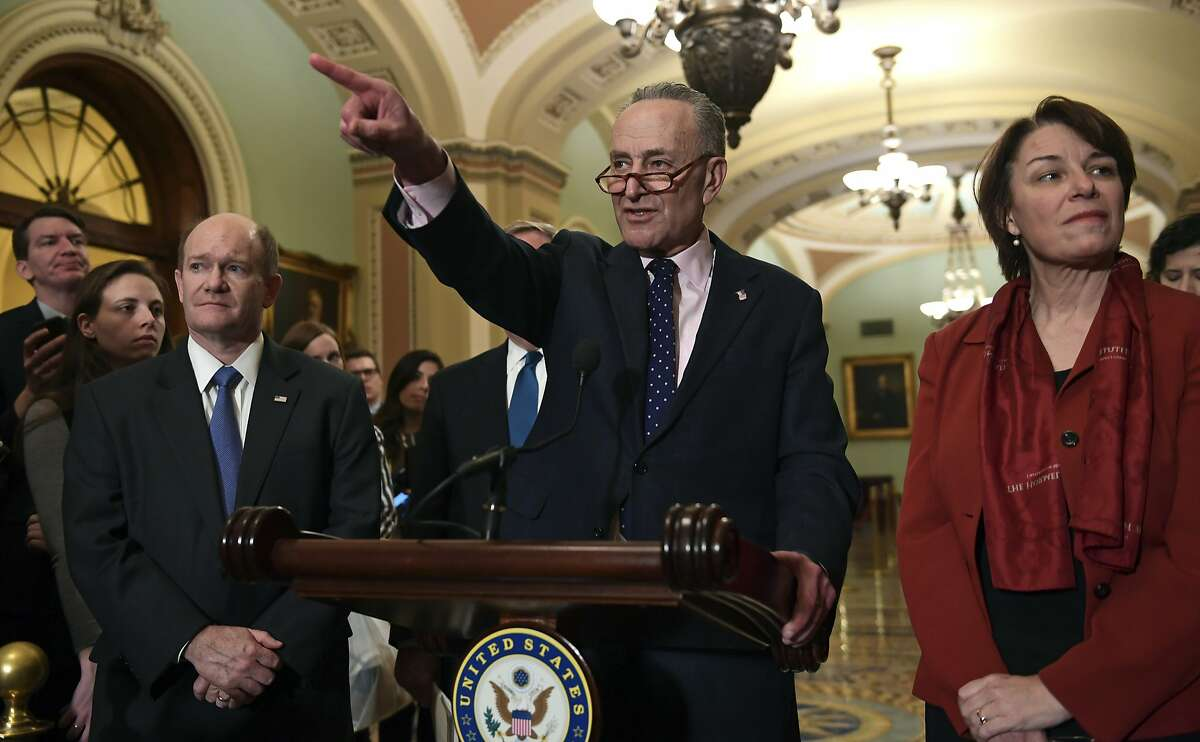 Senate Minority Leader Sen. Chuck Schumer of N.Y., center, calls on a reporter on Capitol Hill in Washington, Tuesday, Feb. 13, 2018, following the weekly Democratic policy luncheon. Schumer is joined by, Sen. Chris Coons, D-Del., left, and Sen. Amy Klobuchar, D-Minn., right.
