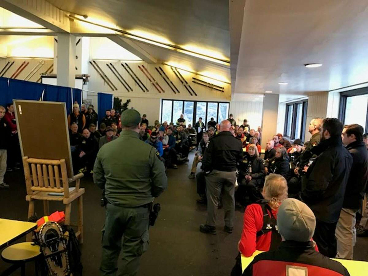 Rescuers and volunteers attend a briefing in the base lodge at Whiteface Mountain during a search for missing skier, Constantinos