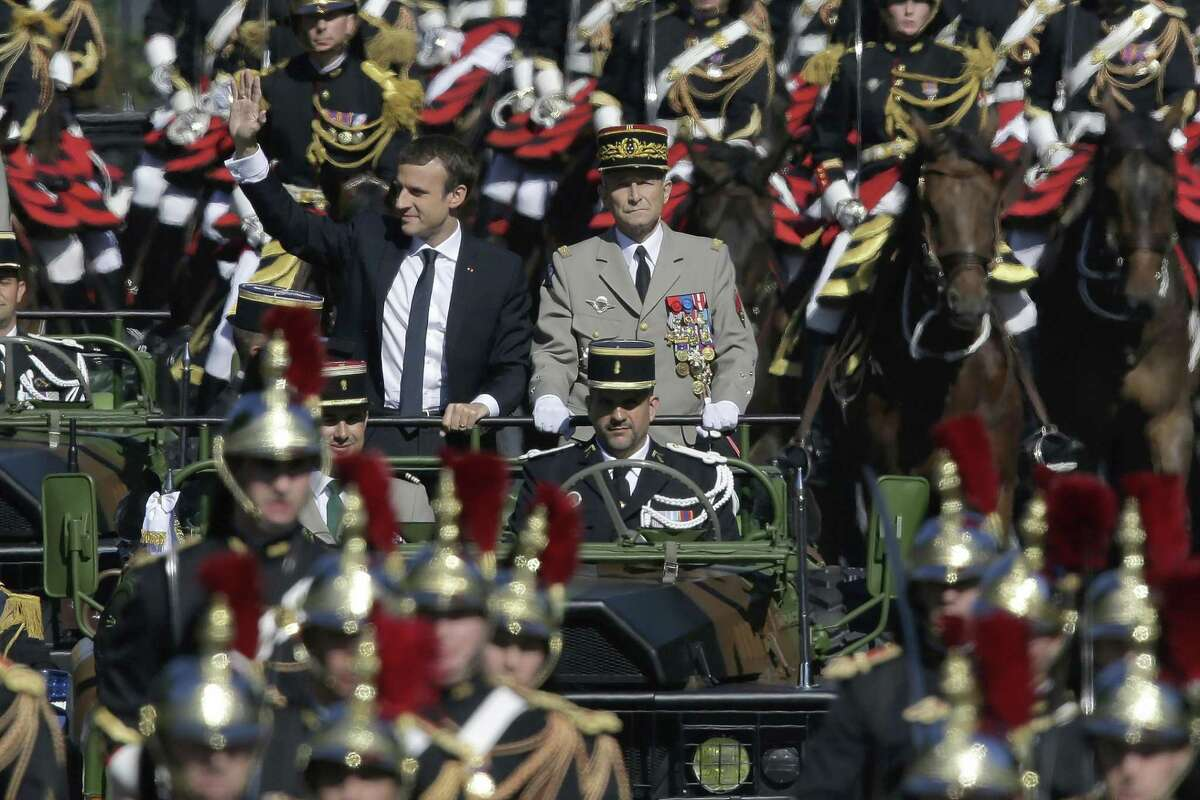 In July, French President Emmanuel Macron, left, and Chief of the Defense Staff Gen. Pierre de Villiers, right, drive down the Champs Elysees avenue during Bastille Day parade in Paris. President Trump now proposes such a military parade going down Pennsylvania Avenue.