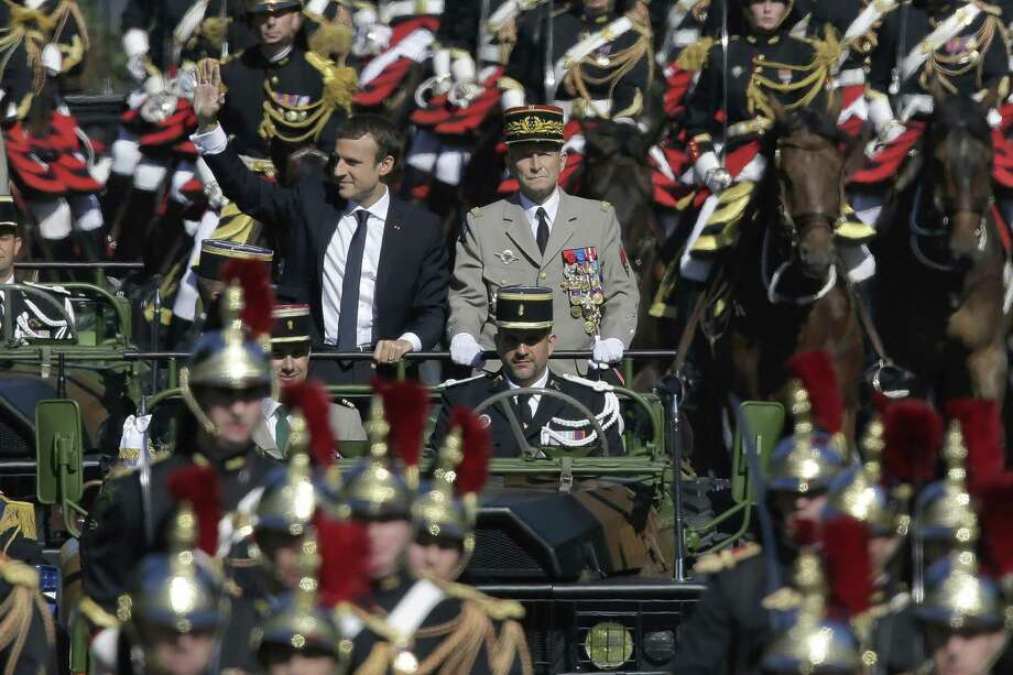 In July, French President Emmanuel Macron, left, and Chief of the Defense Staff Gen. Pierre de Villiers, right, drive down the Champs Elysees avenue during Bastille Day parade in Paris. President Trump now proposes such a military parade going down Pennsylvania Avenue. Photo: Markus Schreiber /Associated Press / Copyright 2018 The Associated Press. All rights reserved.