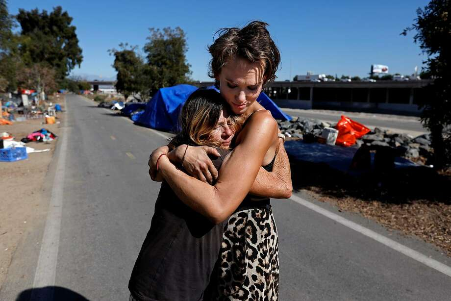 Kathy Schuler, 62 (left), who was released from jail Tuesday after being arrested for camping, is given a hug by her granddaughter, Ashley Foster, at their homeless encampment in Anaheim. Photo: Gary Coronado, TNS