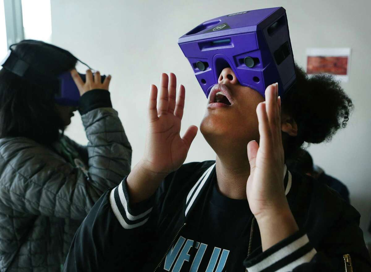 Jessica Willis, right, and Azucena Valdez, both students at Henry Ford Academy, react to a view in a virtual reality space mission to Mars presented by the Alamo Colleges' Scobee Education Center at the Confluence Summit. SAWS sponsored more than 900 high school students from public and private schools across the city to participate in its seventh annual Confluence Summit at the Witte Museum on Tuesday.