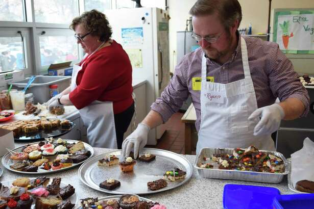 Spectrum/Kent Center School Scholarship Fund board members Maureen Smith and Ryan Carr prepare platters of chocolate treats at the scholarship fund's 23rd annual Chocolate Fest held at Kent Center School FEb. 8, 2018.