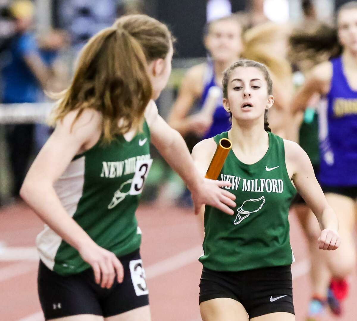 New Milford's Brooke Morabito hand's off the baton to Darcy Cook in the 4 x 800 Meter relay during the CIAC Class L state Championships in New Haven.