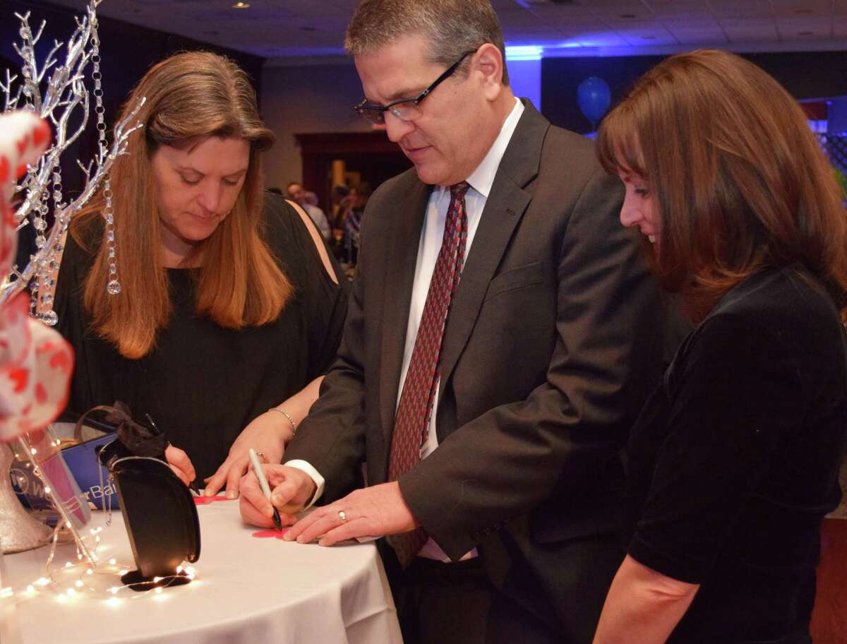 Greater New Milford Chamber of Commerce Executive Director Denise Del Mastro, left, helps Chamber second vice president Kirk Englund and his wife, Kathy, fill out a chance to win a necklace at the Chamber's 20th annual Crystal Winter Gala held Feb. 10, 2018 at the Amber Room Colonnade in Danbury.