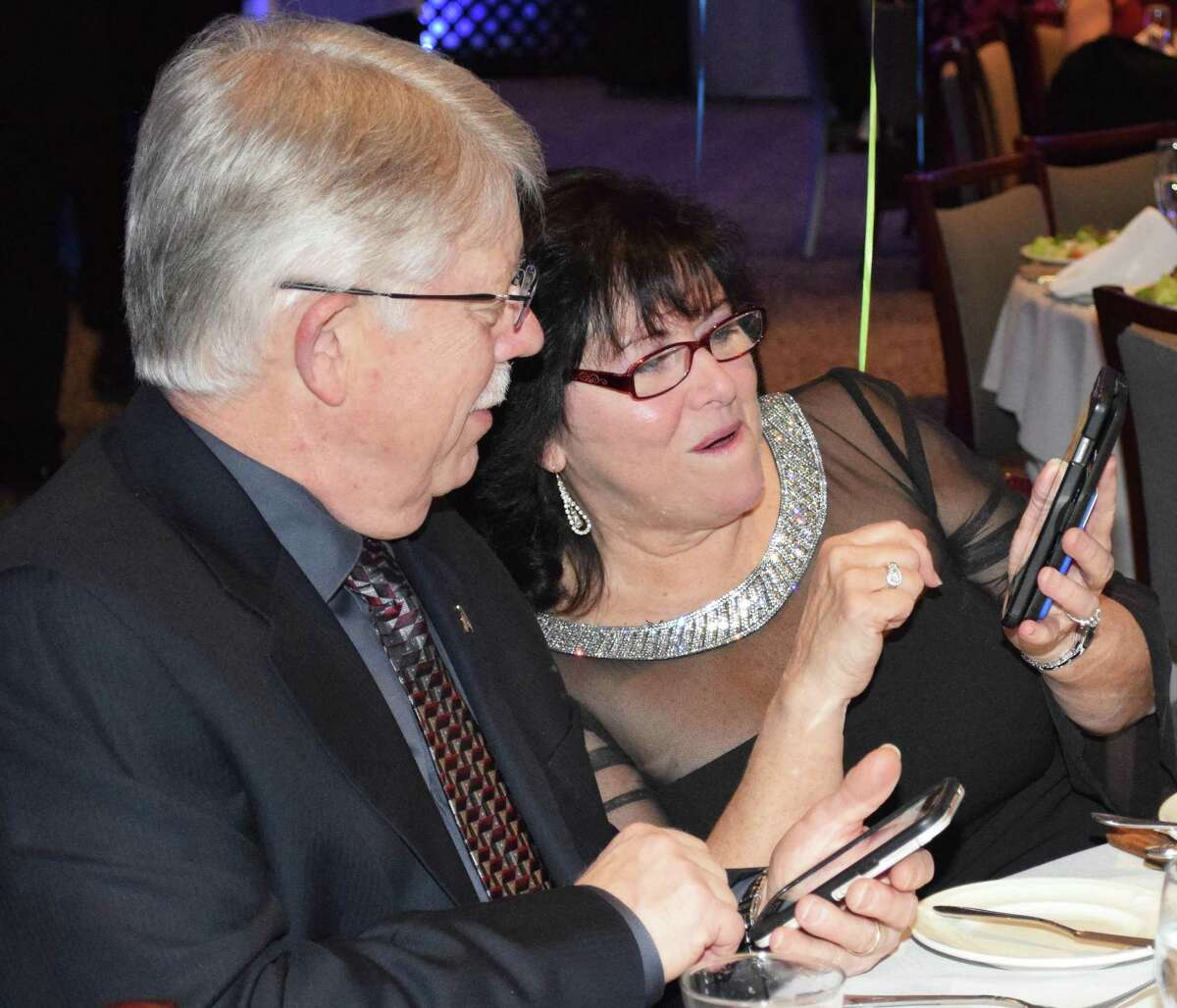 Kathy Hanson of Oakville, who works at Webster Bank in New Milford, and her husband, Ricky, review photographs they snapped at the Greater New Milford Chamber of Commerce's 20th annual Crystal Winter Gala held Feb. 10, 2018 at the Amber Room Colonnade in Danbury.