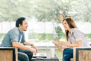 Young Asian couple or coworker talking at coffee shop or modern office, garden background. With laptop notebook, smartphone and digital tablet. Modern lifestyle with computer gadget technology concept