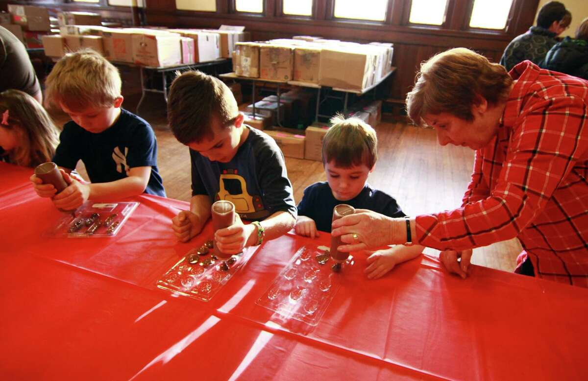 Volunteer Vivian Palsa helps Logan Gryga, 4, make his chocolate candies during Pequot Library's Kids' Candymaking Workshop in Southport, Conn., on Tuesday Feb. 13, 2018. Making candies with Logan is his older brother Kyle, 6, at far left, and friend Jackson Simonis, 7. Kids from kindergarten to 8th grade were able to make chocolate treats for Valentine's Day. They were also able to use crafts to create their own gift box and card. For future events or information, visit: www.pequotlibrary.org