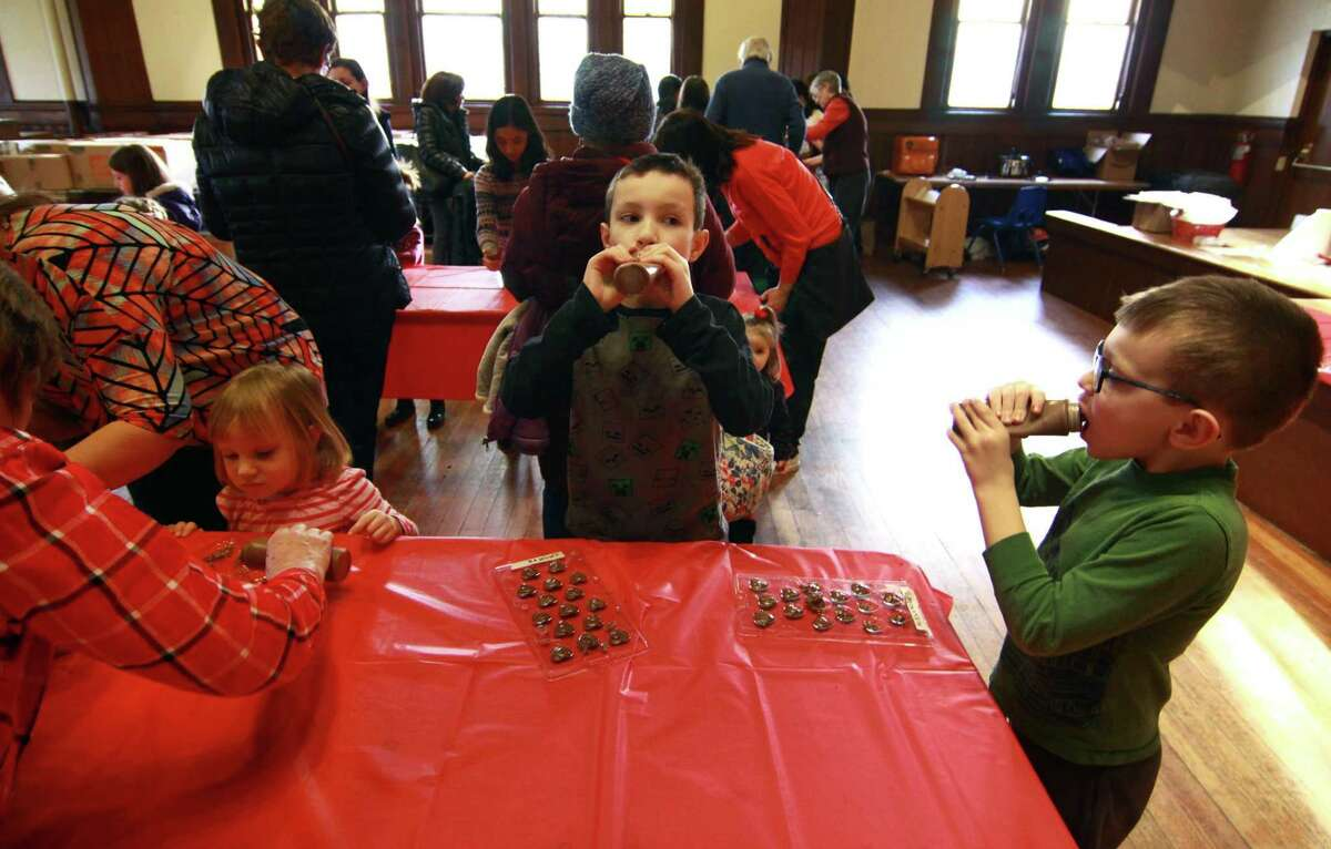 Vincent Murphy, 8, of Monroe, in center, and his brother Alexander, 6, eat chocolate between making their candies during Pequot Library's Kids' Candymaking Workshop in Southport, Conn., on Tuesday Feb. 13, 2018. Kids from kindergarten to 8th grade were able to make chocolate treats for Valentine's Day. They were also able to use crafts to create their own gift box and card. For future events or information, visit: www.pequotlibrary.org