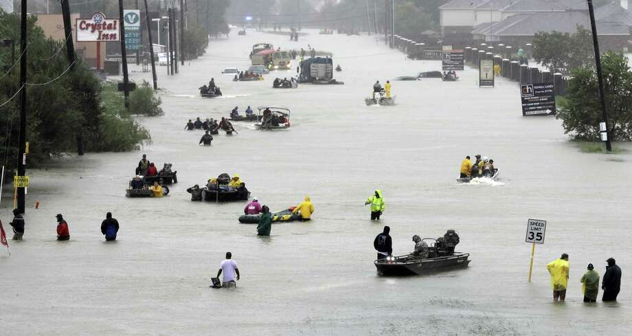 In this Aug. 28 photo, rescue boats float on a flooded street as people are evacuated from rising floodwaters brought on by Tropical Storm Harvey in Houston. Texas Gov. Greg Abbott says communities that were hit hard by Hurricane Harvey will be able to apply for federal funds that can be used on projects to help prevent or lessen damage from future storms. Photo: David J. Phillip /Associated Press / Copyright 2018 The Associated Press. All rights reserved.