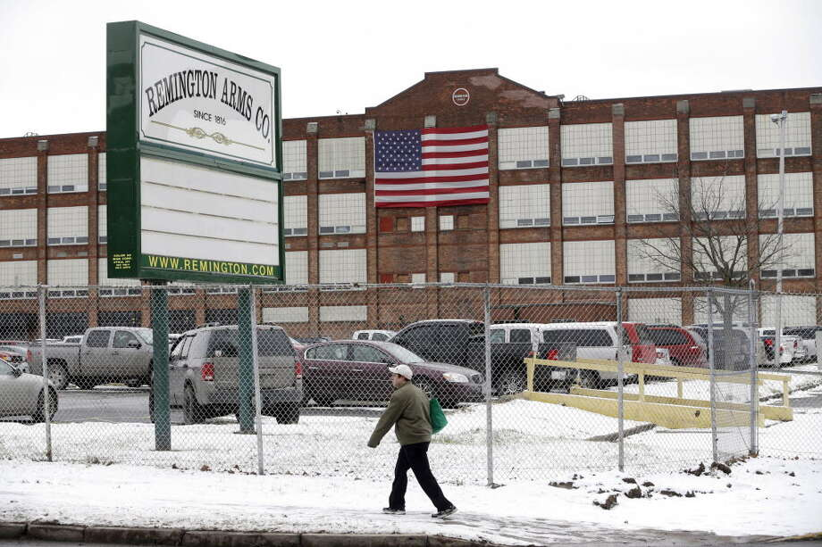 In this Thursday, Jan. 17, 2013, photo, a man walks past the Remington Arms Company in Ilion, N.Y. (AP Photo/Mike Groll)