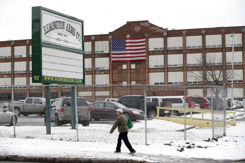 In this Thursday, Jan. 17, 2013, photo, a man walks past the Remington Arms Company in Ilion, N.Y. Remington Outdoor Company announced Monday that it would file for reorganization under Chapter 11 to keep operating while giving creditors control of most equity in the privately-held company as it seeks to restructure its finances. (AP Photo/Mike Groll)