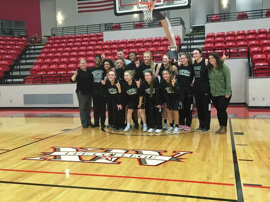 The Kingwood Park Lady Panthers pose in celebration after beating the Lumberton Lady Raiders in the opening round of the playoffs Feb. 13 at Lee College, They hold up two fingers, celebrating their advancing to the second round of the playoffs. Photo: Elliott Lapin