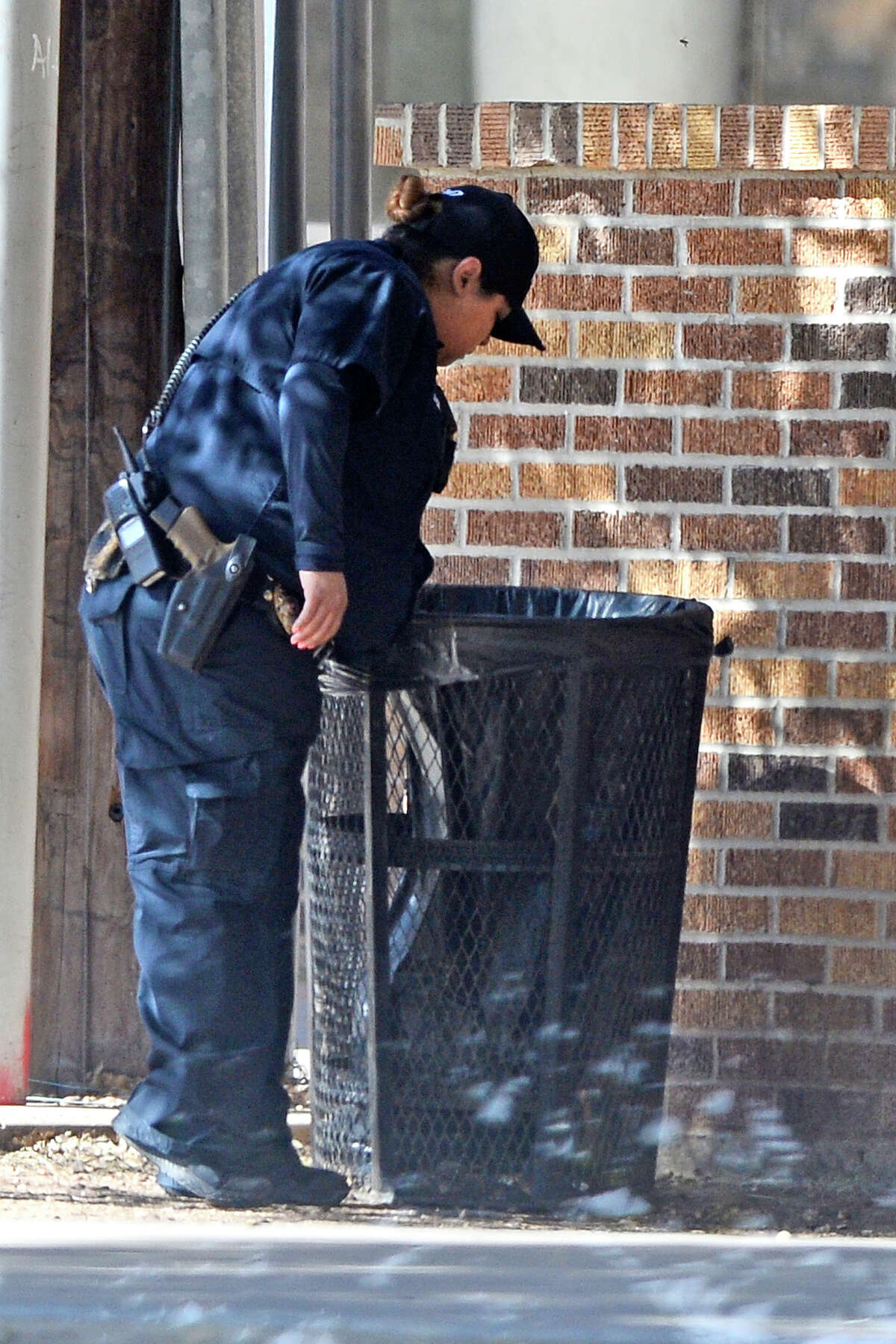 A MISD Police officer looks in a trash can during a lockdown situation on the Midland High campus that was prompted by the reported presence of a weapon at the school, Feb. 13, 2018. James Durbin/Reporter-Telegram