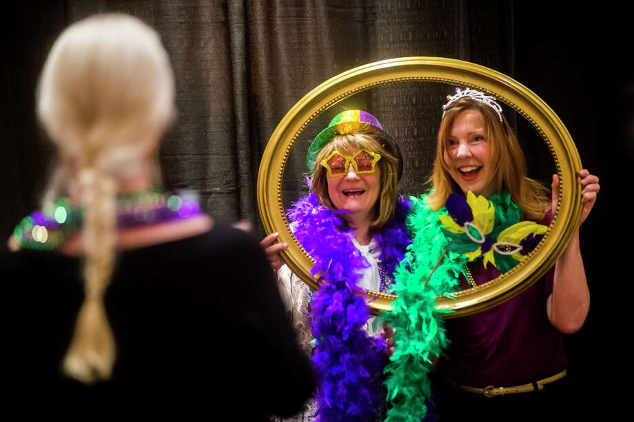 Guests take photos in the photo booth during The Legacy Center's annual Mardi Gras Feast on Tuesday, Feb. 13, 2018 at the Great Hall Banquet and Convention Center. (Katy Kildee/kkildee@mdn.net) Photo: (Katy Kildee/kkildee@mdn.net)