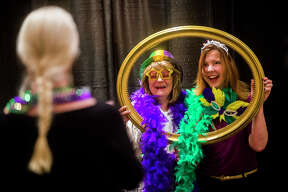 Guests take photos in the photo booth during The Legacy Center's annual Mardi Gras Feast on Tuesday, Feb. 13, 2018 at the Great Hall Banquet and Convention Center. (Katy Kildee/kkildee@mdn.net)